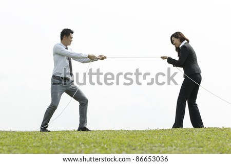 Asian Business people playing tug of war. A Conceptual image. - stock photo
