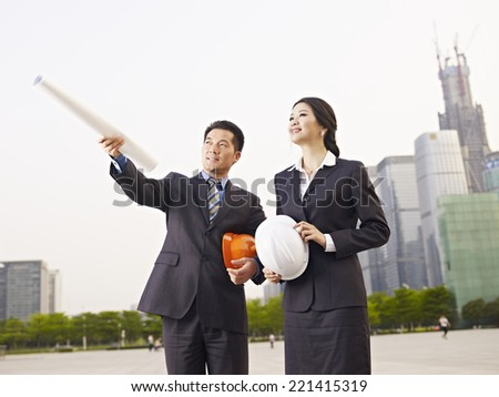 asian business people with safety hats and blueprint. - stock photo