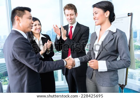 Asian Business Team - applause after an successful presentation in the office - stock photo