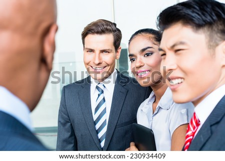 Asian business team discussing and sharing ideas with their Indian boss - stock photo