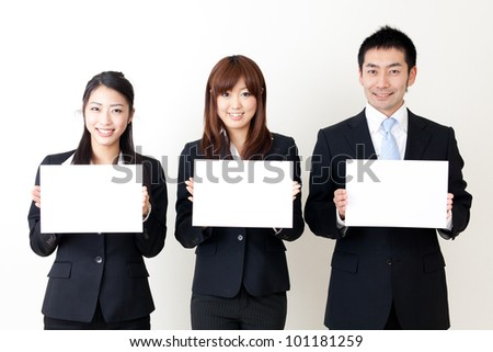 asian business team holding a blank whiteboard - stock photo