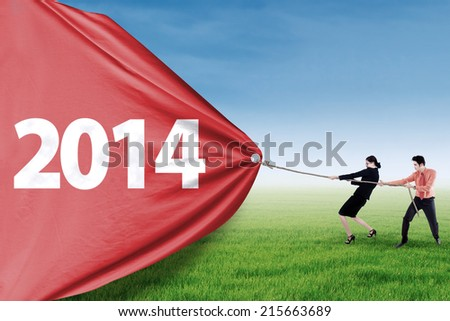 Asian business team is pulling big number of 2014 outdoor - stock photo