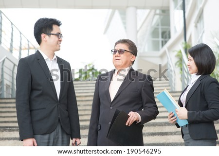 Asian business team meeting, having discussion outside office. - stock photo