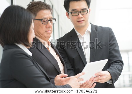Asian business team meeting. Staff explaining and showing report on digital computer tablet to CEO boss over office. - stock photo