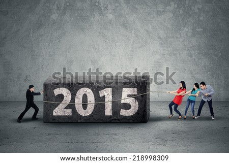 Asian business team move a boulder as an obstacle in 2015 - stock photo
