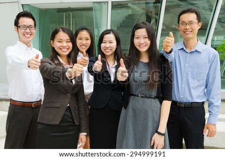 Asian business team raised their thumbs up - stock photo