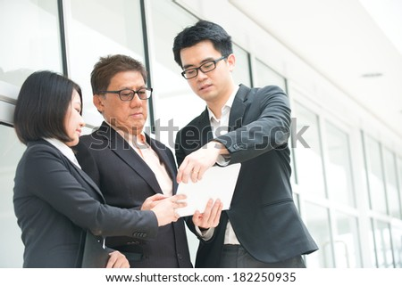 asian business team reporting to senior ceo with office background