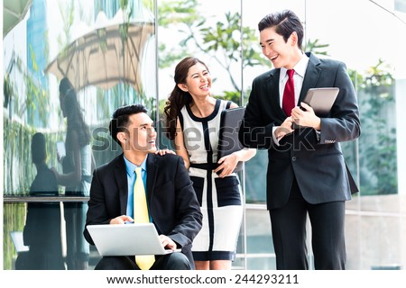 Asian business woman and men working outside on computer  - stock photo