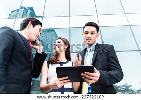 Asian business woman and men working outside with tablet computer and mobile phone
