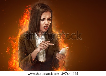 Asian business woman angry looking text on her cellphone - stock photo