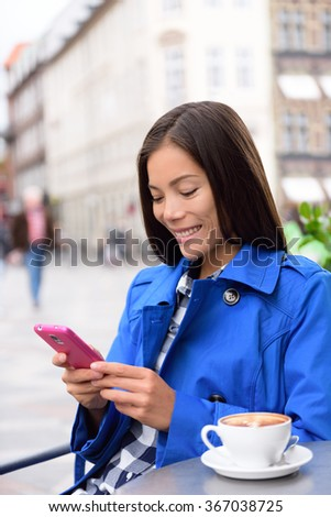 Asian business woman drinking coffee at outdoor terrace cafe texting or reading news on smart phone using app. European city center street of restaurants and cafes in fall autumn. - stock photo