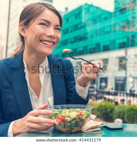 Asian business woman eating healthy salad vegetarian takeaway cafe meal at work during lunch break on outdoor terrace city park in summer. Happy businesswoman having a balanced diet for weight loss.  - stock photo