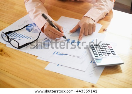 Asian Business woman hand pointing at business document during discussion at meeting and  using a calculator to calculate the numbers. - stock photo