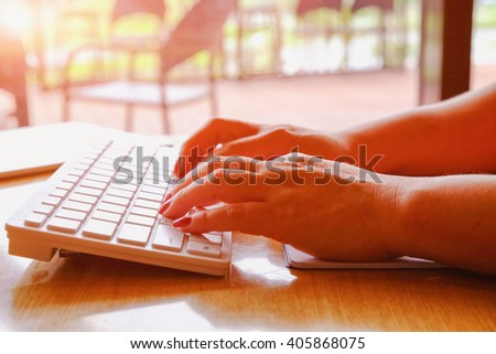 Asian business woman hands typing on a PC or laptop keyboard - stock photo