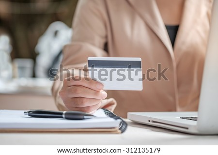Asian business woman holding a credit card and using laptop for online shopping. - stock photo
