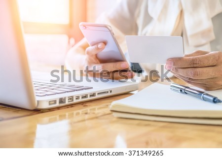 Asian business woman holding a credit card and using smart-phone for online shopping.vintage tone Retro filter effect,soft focus,low light.(selective focus) - stock photo