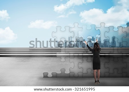 Asian business woman holding piece of puzzle trying to build a city. Business development concept