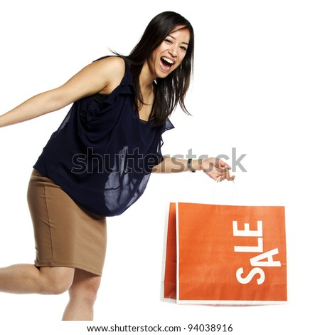 Asian business woman holding shopping bag smiling - stock photo