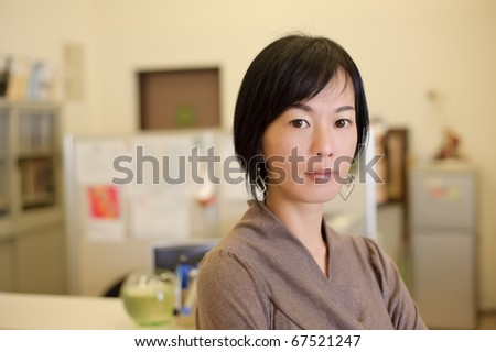 Asian business woman in office, closeup portrait.