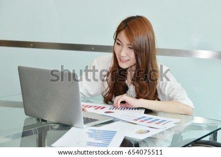 Asian business woman is using laptop in an office