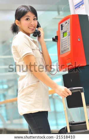 asian business woman making a call at airport - stock photo