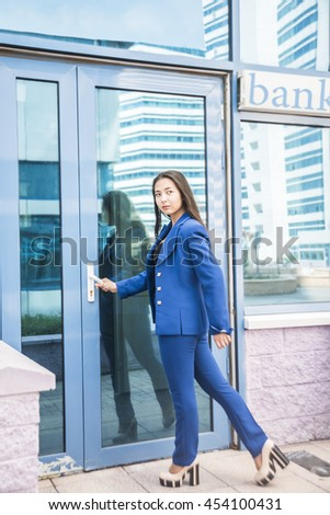 Asian Business woman, opens the door of bank office building. Reflection in glass. Businesswoman wear blue stylish suit. Girl look at far away. - stock photo
