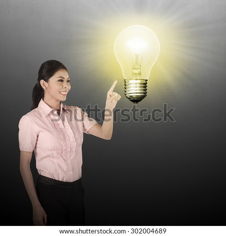 Asian business woman pointing lamp bulb. Business idea concept