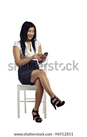 Asian business woman reading a message on her cell phone sitting against white background - stock photo