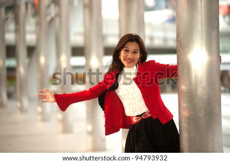 Asian business woman rejoice with arms outstretched . - stock photo