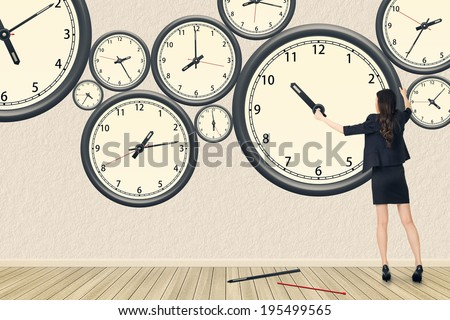 Asian business woman repair the clock, concept of time management, rebuild, busy etc. - stock photo
