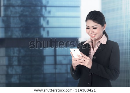 Asian business woman send text via phone with office building background - stock photo