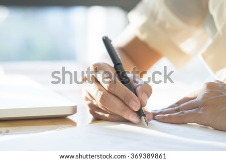 Asian Business woman signing a contract document making a deal, selective focus. - stock photo
