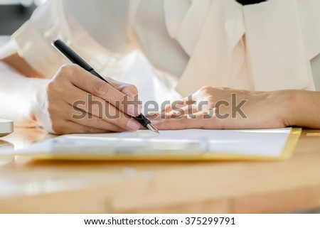 Asian Business woman signing a contract document making a deal. Vintage tone, Retro filter effect, Soft focus, Low light.(selective focus)  - stock photo