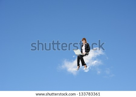 Asian business woman sit on cloud and use laptop over blue sky. Concept of cloud, work, network or new technology in business. - stock photo