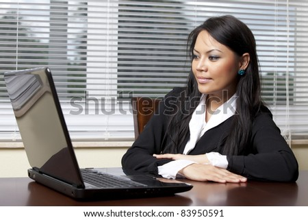 Asian business woman sitting at desk looking at computer screen - stock photo