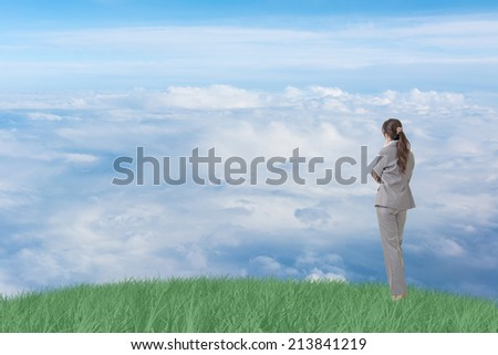 Asian business woman standing on grassland and thinking with copyspace on heaven.