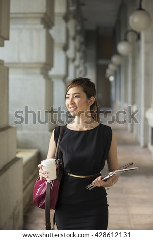 Asian business woman standing outside with office buildings in the background. Portrait of a Chinese business woman looking at the camera. - stock photo