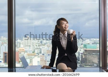 Asian business woman take a break in hotel room. - stock photo