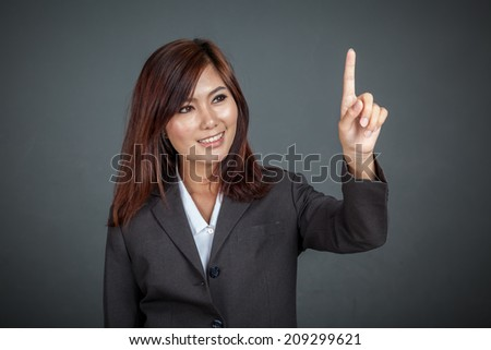 Asian business woman touching the screen and smile on gray background - stock photo