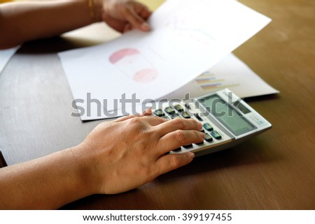 Asian Business woman using a calculator to calculate the numbers - stock photo