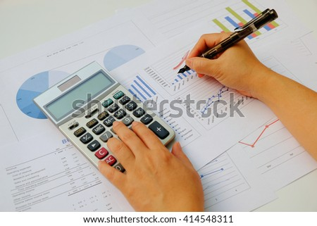 Asian Business woman using a calculator to calculate the numbers