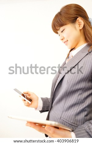 Asian business woman using a smartphone and tablet in a office with suit