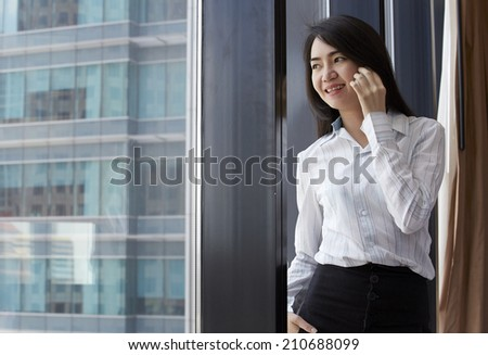 Asian business woman using cellphone in the big city.