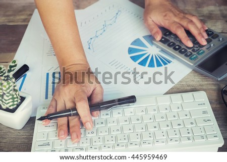 Asian Business woman using computer calculator to calculate the numbers vintage tone - stock photo