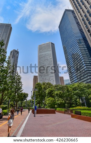 Asian business woman waling Tokyo business district at daytime - stock photo