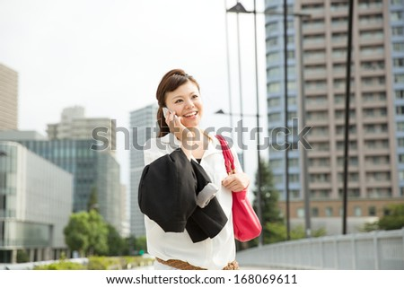 Asian business woman walking outside her office - stock photo