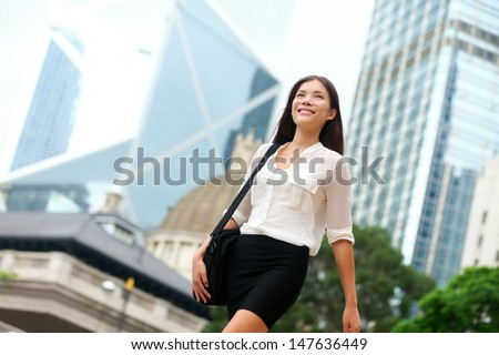 Asian Business woman walking outside in Hong Kong. Asian businesswoman office worker in downtown business district. Young multiracial Chinese Asian / Caucasian female professional in central Hong Kong - stock photo