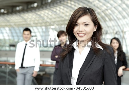 Asian Business woman with colleagues in the background out of focus