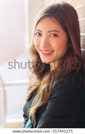 Asian business woman with smiling face, blurred background
