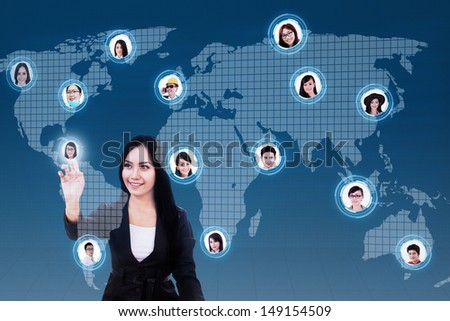 Asian business woman with social networking lcd screen against world map background - stock photo
